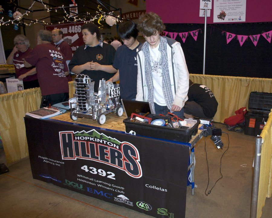 Team members Ian Randall, Tony Gao, and Nick VanBeek make some final tweaks to the robot before a match. Photo provided by team.