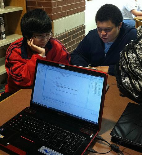 Robotics Club members Ian Randall and Jerry Zhang work on the programming of their robot in the library for their upcoming competition on December 17th. Photo by Emma Johnson