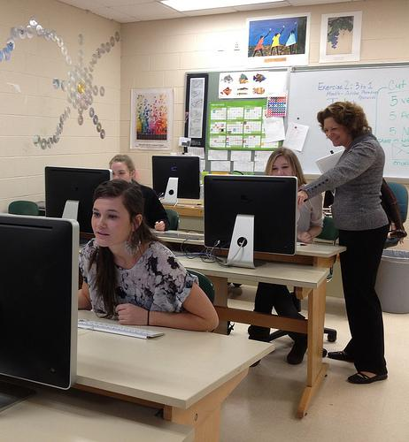While the other students work diligently, Ms. Brayer helps Lily Whitehouse design a page for the yearbook. Photo by Emily Coburn