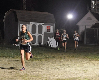 Hopkinton runners Shelby Aarden, followed by Melissa Lodge, race at the Twilight Cross Country Invitational on Saturday. The girls 5th and 7th place finishes contributed to the teams overall 5th place finish. Photo by Samantha Lee