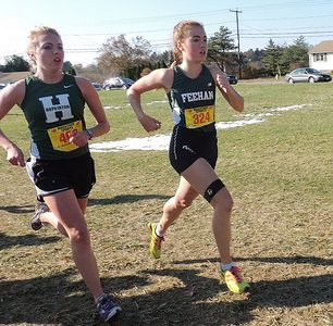Junior Melissa Lodge (left) rounds a corner at the Division IV state meet on Saturday. Her fourth place finish contributed to the teams second place win. Photo by Samantha Lee