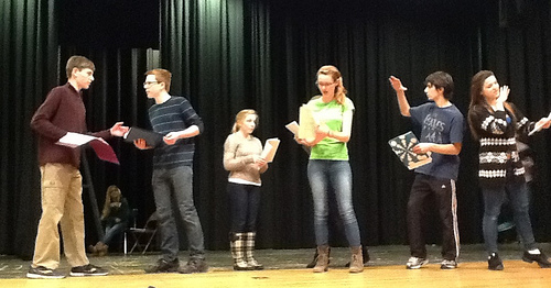 Evelyn Oliver (center), playing Alice Little, and other cast members (left to right) Erik Fliegauf, Jack McCauliffe, Ashley Olafsen, Henry Vumbaca, and Taylor Forsmo prepare the Growing and Shrinking scene for the original HHS production of Uncommon Nonsense. The scene is based in a theatrical game in which a new actor enters the stage to create a new scene. As more players are added and new scenes emerge, they eventually exit the stage and the scenes are recycled. Photo by Blair Guild