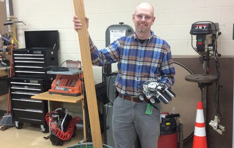 Mr. Scott in room 207 holding projects being worked by students. Photo by Charlie frank.