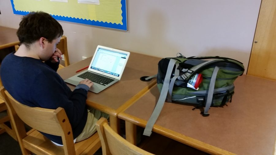 Senior Trevor Perkins using his laptop to study for his government midterm during a free period in the library.