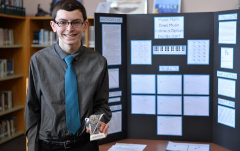 Junior Brian Best proudly stands beside his third-place winning project,
