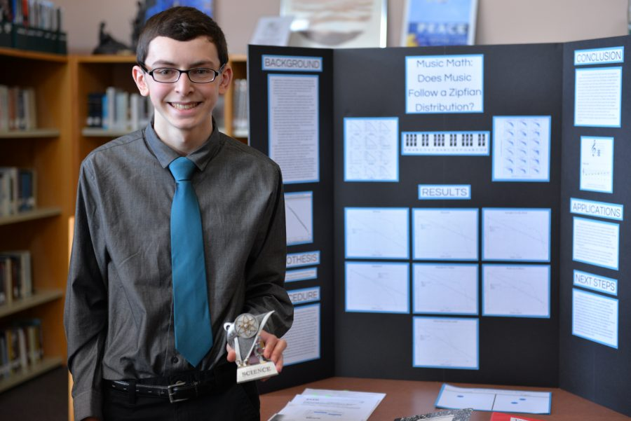 Junior Brian Best proudly stands beside his third-place winning project, Music Math: Does Music Follow a Zipfian Distribution? Photo courtesy of Fred Haas.