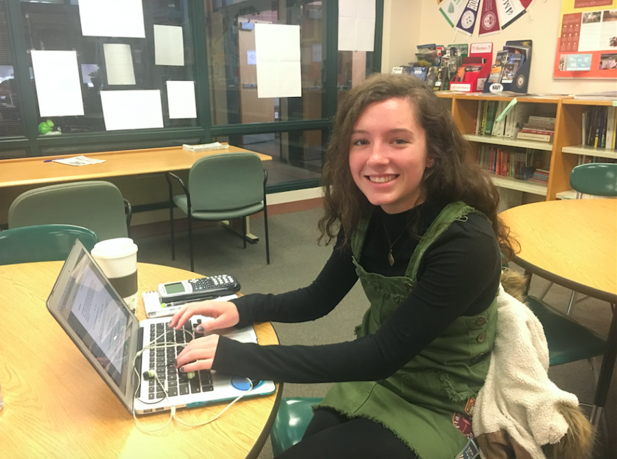 Photo: Rachel Gooley smiling while she types on her computer