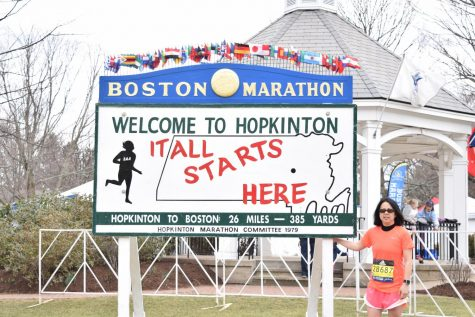 "Photo: Denise Antaki standing in front of the ""It All Starts Here Sign"" two days before Marathon Monday."