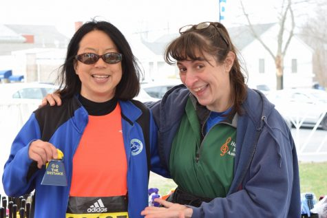 Photo: Denise Antaki (left) visiting Kathy Curry's (right) booth at Hopkinton Common where she is selling bells to cheer the runners on.