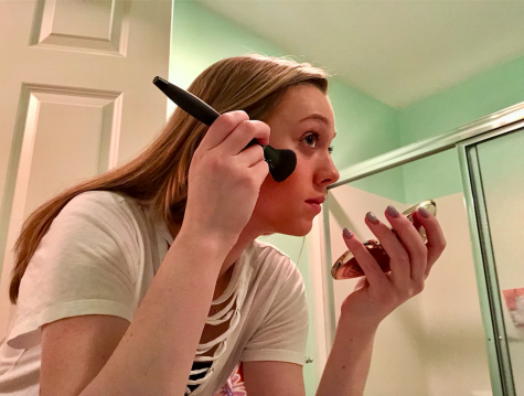 Photo: Caroline Murphy is applying makeup to her face