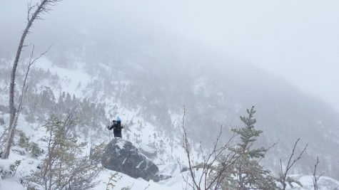 Photo: Lu Wang scaling a rock in the blizzard.