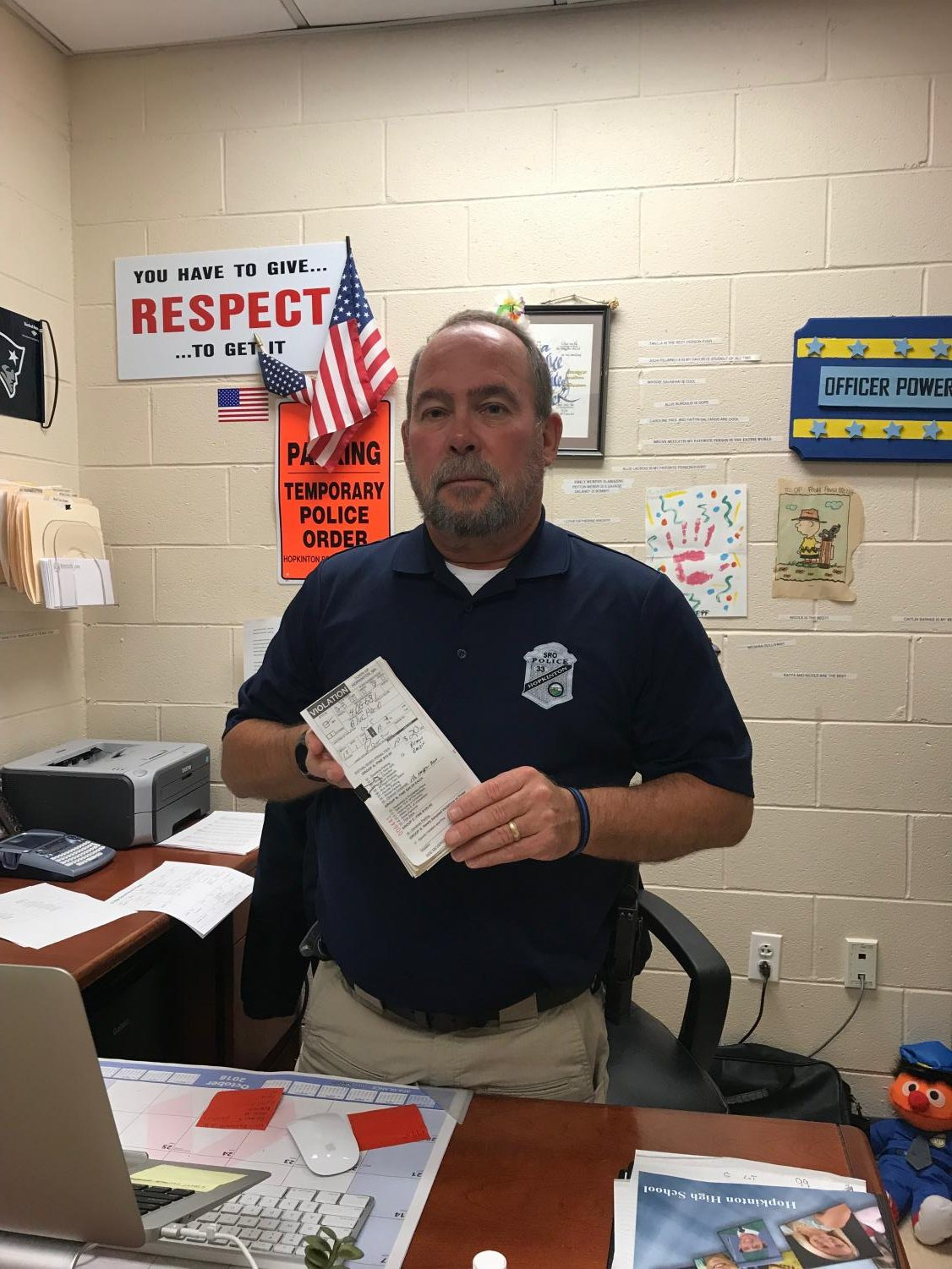 Officer Powers holds the parking tickets he issues out.