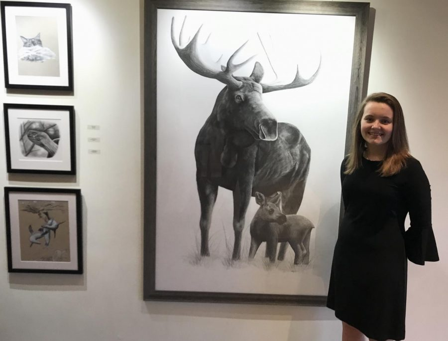 Junior+Maddie+Mezitt+poses+in+front+of+her+incredible+pencil+drawing+of+a+moose+and+its+calf+during+the+2019+HHS+Art+Department+Honors+Exhibition+at+the+Hopkinton+Center+for+the+Arts+%28HCA%29.+Mezitt+is+a+silver+key+winner+in+the+2019+scholastic+art+competition+for+her+drawing+%E2%80%9Cstairs%E2%80%9D+that+was+not+on+display+at+the+art+showcase.+Mezitt+also+was+awarded+two+honorable+mention+awards+in+the+same+competition+for+her+illustrations+%E2%80%9CGalapagos+Giant%E2%80%9D+and+%E2%80%9CAsiago+Donkey.%E2%80%9D