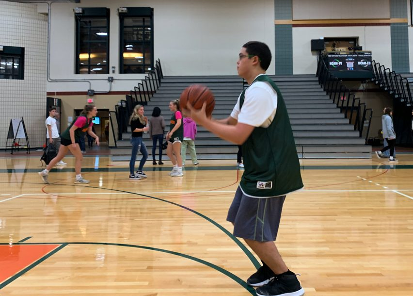 """Centered, Peishoff lets a three pointer go as he warms up for the Hillers game against Nipmuc on Tuesday, October 29. The Hillers earned their first ever win, and Peishoff had the game-clinching steal as the Hillers held on to a 67-66 victory. """"We were up by a point and I knew we had to keep going,"""" said Peishoff. """"That win meant a lot for me and I hope we can get another one next week against Holliston."""""""