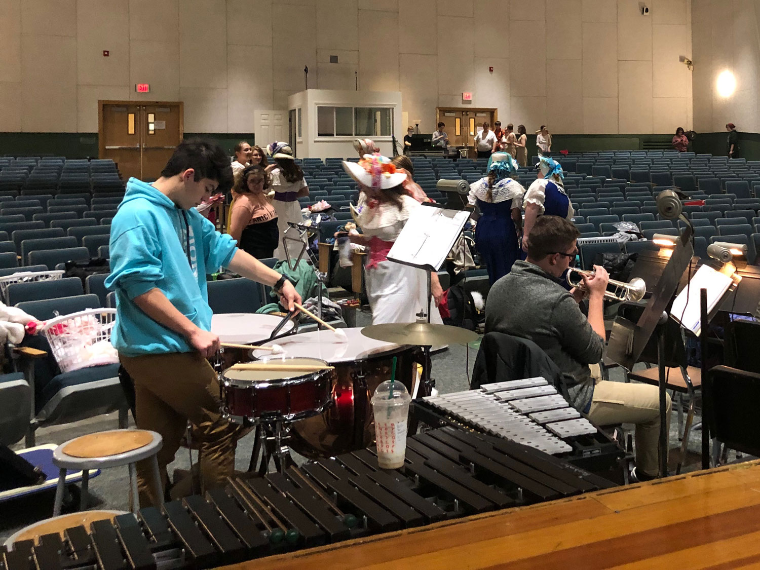 Members of the pit orchestra warm up and get ready for the first