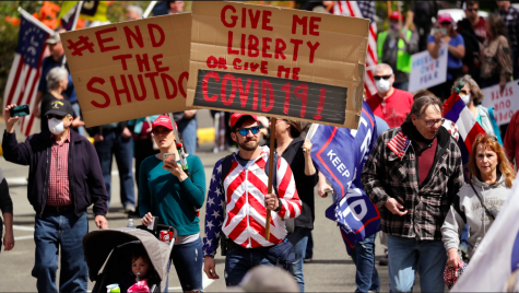 Gathered to protest the stay-at-home order in Washington state, people get creative with their signs. The stay-at-home order is to try and combat the spread of the illness, yet most of the people pictured are not wearing masks or gloves.