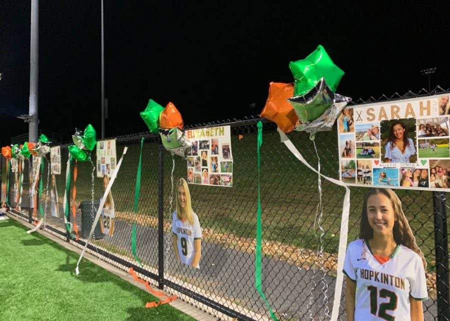 Senior night decorations set up by underclassmen. Cardboard cutouts and collage posters are made for the event every year. Hopkinton colored balloons line the fence